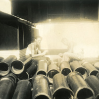 Two soldiers seated alongside rows of metal piping