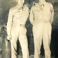 Two soldiers pose for a photograph in-doors