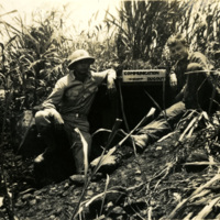 Two soldiers sitting next to a sign