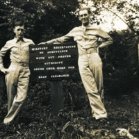 Two soldiers stand by a sign of rules and regulations