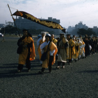 Marchers in robes with buddhist banner
