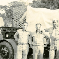 Three soldiers pose by a military vehicle