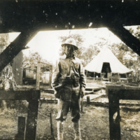 A picture of a soldier with tents behind him