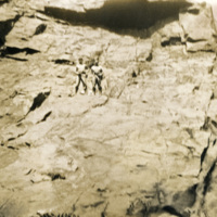 Two men standing on top of a rocky formation
