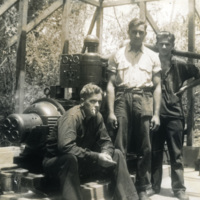 Daniel Klapproth stands by an engine with two other soldiers