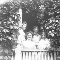 Three women and Baldwin boy on porch