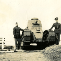 Two uniformed soldiers stand beside a tank