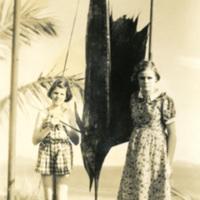 Two girls pose next to a hanging fish