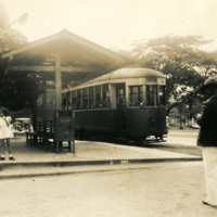 People standing around a small tram station