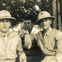 Three men are seated with their eyes on the camera