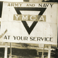 A soldier stands by a YMCA sign