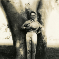 A man poses by a tree