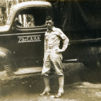 A soldier stands beside a truck