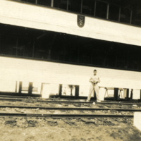 A soldier is standing on train tracks
