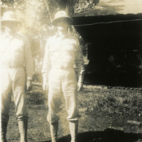 Two soldiers pose for a photograph in uniform