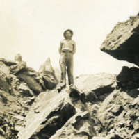 A soldier stands on top of a rock formation