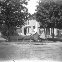 Two women on tandem bike, 56 Street