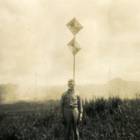 A soldier stands in front of a sign