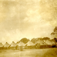 Soldiers stand around a row of tents