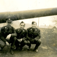 Four soldiers pose by a cannon