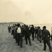 A large group march along the beach
