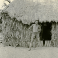 A shirtless man standing by a hut