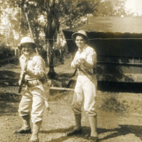 Two soldiers pose with rifles in their hands