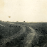 A dirt road and grassy field