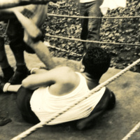 A soldier is on the floor of a boxing ring