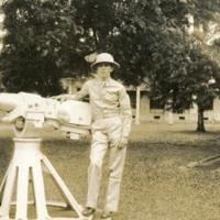 A soldier stands beside a decorative gun