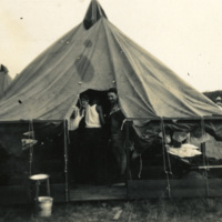 Soldiers stand in a tent entryway