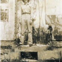 A soldier stands between two buildings