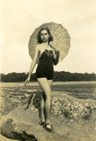 A woman poses with an umbrella in her hand