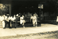 Two women and three men seated on a bench