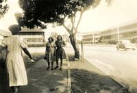 Three women walking down a sidewalk