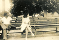 Two people seated on a public bench