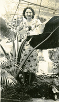 A woman poses by a plant