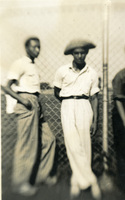 Two men leaning against a fence